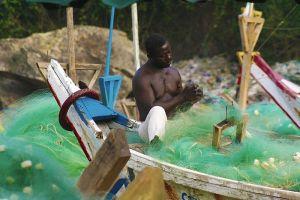 A fisherman mends his nets, Cape Coast, Ghana.